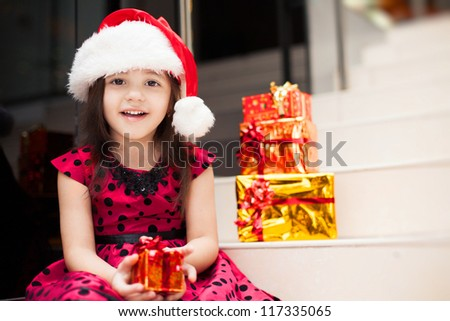 Cute little girl posing with gifts in the Christmas hat and a luxurious dress, sitting on the stairs in a big shopping mall.