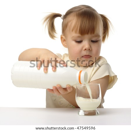 Cute little girl pouring milk in glass, isolated over white