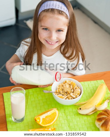 cute little girl pours milk in cereal