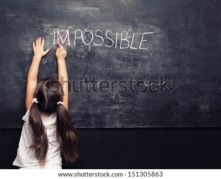 Stock Photo cute little girl putting a cross over impossible on blackboard