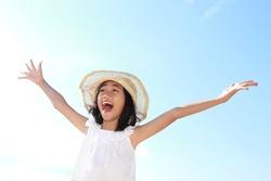 Cute little girl raises her hands against blue sky