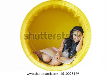 Cute little girl resting on a yellow circular sofa on the wall.