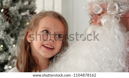 Cute little girl singing Christmas song together with Santa Claus #1104878162