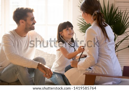 Cute little girl sit on couch with dad holding stethoscope listen to visiting doctor or nurse chest, happy young family have fun at home playing funny game with preschooler daughter relaxing together