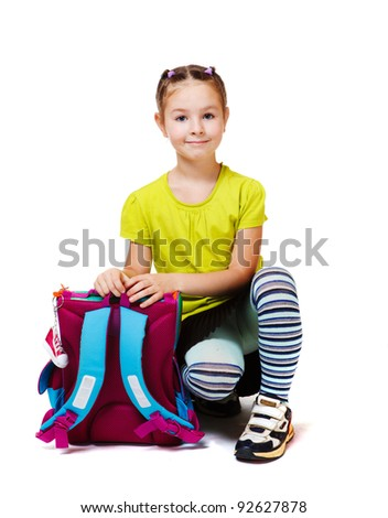 Cute little girl sits with backpack