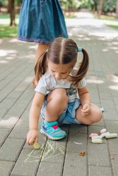 Cute little girl sitting and drawing with chalk on asphalt in park.