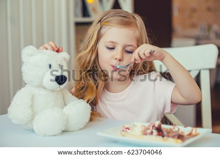 Cute little girl sitting at a table in a cafe and feed a favorite toy Bear ice cream.Happy child Zdjęcia stock ©