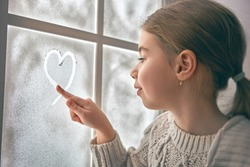Cute little girl sitting by the window and drawing heart on frozen glass. Kid enjoys the winter.