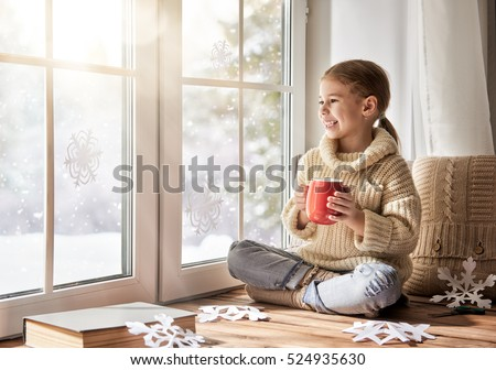 Cute little girl sitting by the window, drinking warm beverage and looking at the winter forest. Child makes paper snowflakes for decoration windows. Kid enjoys the snowfall.