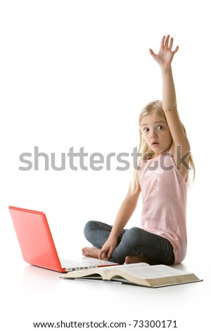 cute little girl sitting down with laptop and book raising her hand isolated on white background