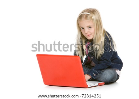 Cute little girl sitting down with laptop isolated on white background - stock photo