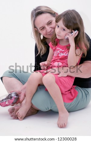 Cute little girl sitting in her mother's lap while talking on a cell phone. Isolated against a white background