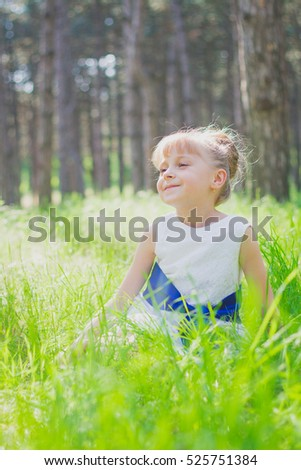 cute little girl sitting in the grass in the woods, around the trees and greenery, warm summer sun warms it, a good mood, relaxation #525751384