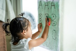 Cute little girl sitting indoor learning drawing letters on paper.