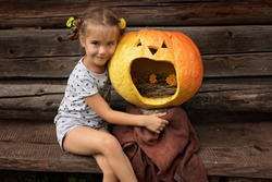 Cute little girl sitting near the crying Halloween pumpkin over old wooden wall, keep calm, funny creative image, outdoor portrait