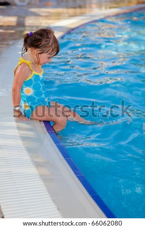 Cute little girl sitting near the swimming pool