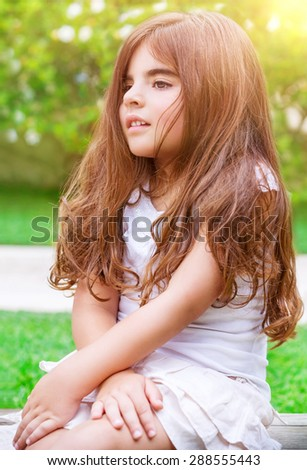 Cute little girl sitting on backyard in bright sunny day, spending summer holidays in summer camp, happy healthy childhood