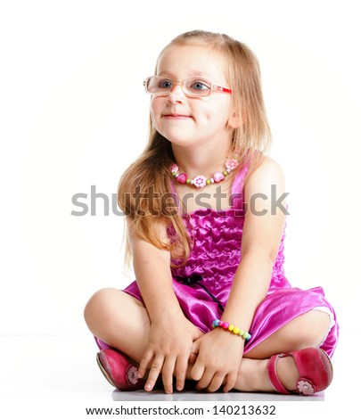 cute little girl sitting on floor and smiling, studio shot isolated on white background