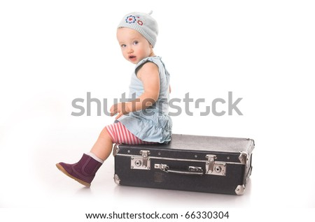 cute little girl sitting on the black suitcase
