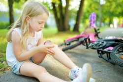 Cute little girl sitting on the ground after falling off her bike at summer park. Child getting hurt while riding a bicycle. Active family leisure with kids.