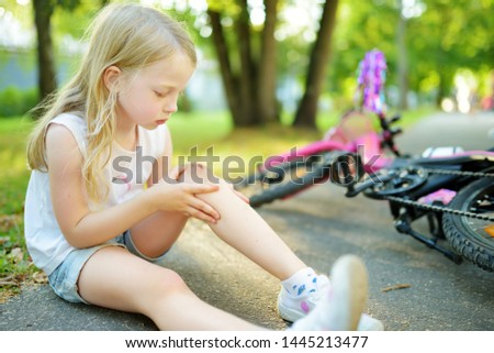 Cute little girl sitting on the ground after falling off her bike at summer park. Child getting hurt while riding a bicycle. Active family leisure with kids. Stockfoto ©