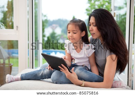 Cute little girl sitting with her mother on couch using a digital tablet