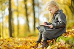 Cute little girl sketching outside on beautiful autumn day. Happy child playing in autumn park. Kid drawing with colourful pencils. Autumn activities for children.