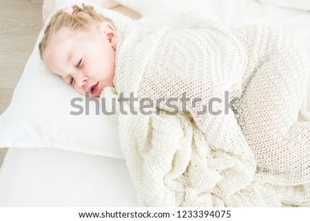 Cute little girl sleeping covered in white blanket. #1233394075