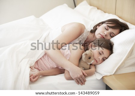 Cute little girl sleeping with mother in bed - stock photo
