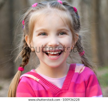 cute little girl smiling in a park close-up