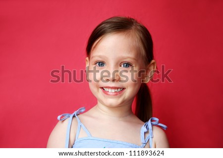 Cute little girl smiling over bright pink background