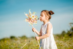 Cute little girl smiling summer in the field holding a windmill