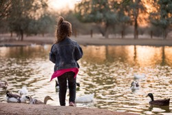 Cute little girl stand near lake with birds
