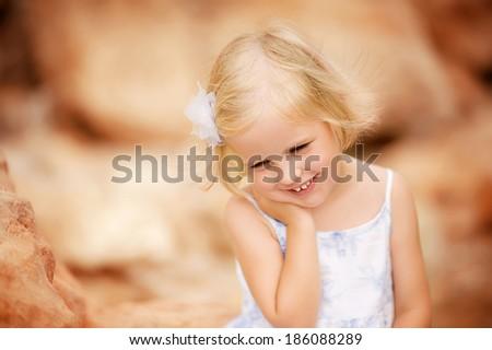 Cute little girl standing in a white dress on the beach. Portrait, eyes closed, a flirt. #186088289