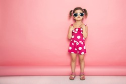Cute little girl standing in pink jumpers and sun glasses on the pink background in the studio. Summer, fun and vacations concept