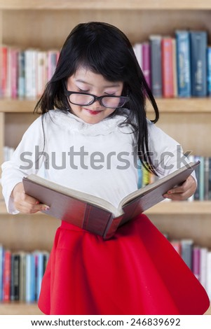 Cute little girl standing in the library while reading a textbook