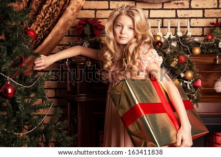 Cute little girl standing with a gift at home near the fireplace and Christmas tree.
