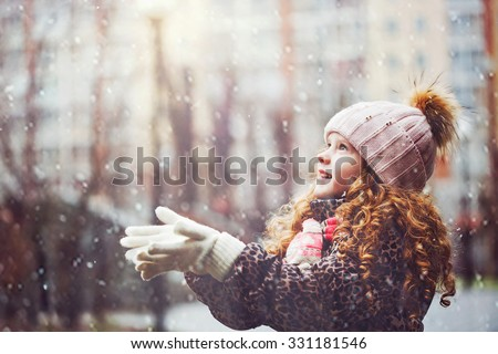 Cute little girl stretches her hand to catch falling snowflakes. First snow. Toning instagram filter.