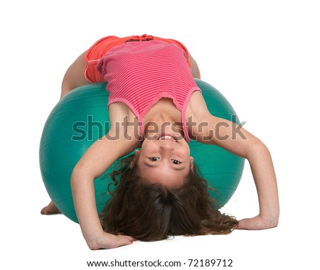 Cute little girl stretching on pilates ball