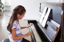 Cute little girl studding to play piano