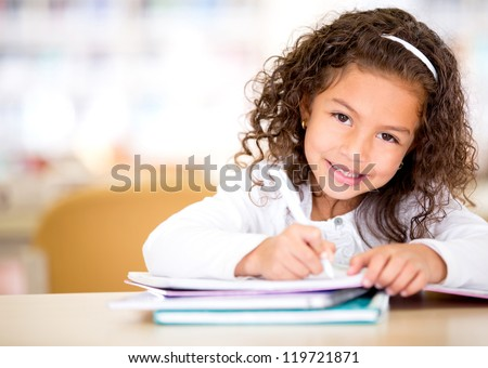 Cute little girl studying at the library and smiling #119721871