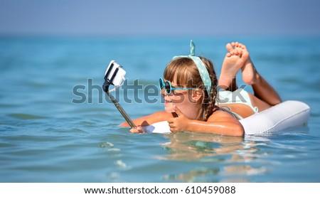 Cute little girl taking selfie using smartwatch. #610459088