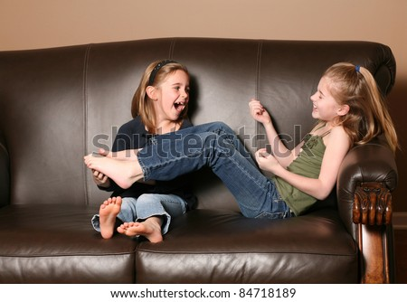 cute little girl tickling sister's feet - stock photo