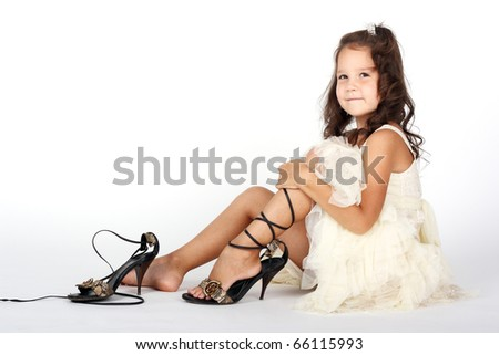 cute little girl trying on her mother's shoes - stock photo