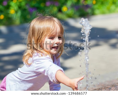 Cute little girl trying to catch the water from the fountain