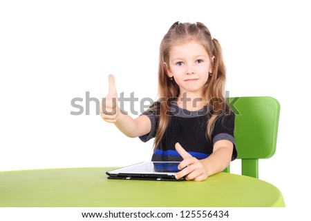 cute little girl using tablet PC with the thumbs up
