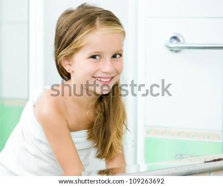 Cute little girl washing in bath. Reflection in the mirror