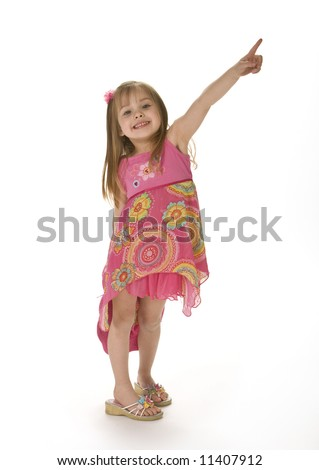 Cute little girl wearing a pink sumer dress smiling and pointing up, isolated on white background.