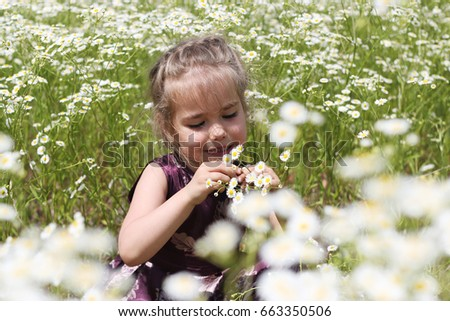 Cute little girl wearing beautiful dress stays among chamomile field playing he loves me he loves me not, pretty girl tearing off petals, beauty and fashion, happy childhood, summer vacation, outdoor #663350506