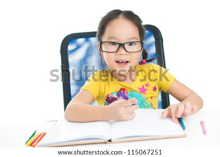 Cute little girl wearing big eyeglasses doing homework